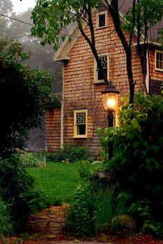English Country Home.  I don't know what it is about this....the dewy, fresh rain you can almost smell, the green, green grass, the soft outdoor lamp that leads the way into this warm, cozy home....