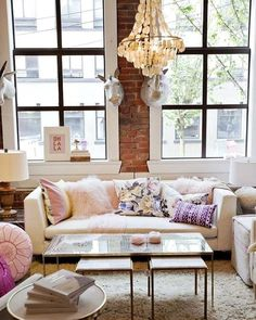 Whimsical and feminine. #pink #interiordesign #pillows #sofa #chandelier #nyc #apartment