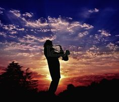 The saxophonist plays a saxophone Harmony of sounds of a saxophone and beauty of the nature sunset Stock Photo
