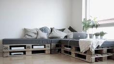 canapé d'angle en palette de bois brut, galettes de siège gris taupe et coussins assortis