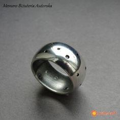 Awangardowa obrączka wykonana ręcznie wg tradycyjnych technik jubilerskich ze srebra pr. 930. Nuta surowości jednak pozostała-srebro jest oksydowane i szorowane a wierzch jest polerowany na połysk. Otwory zrobione ręcznie. Szerokość obrączki- 1 cm. Rozmiar jubilerski 12,5. Przy obłym kształcie będzie pasowała na palec rozm. 11,5-12. Polecam więc na palec serdeczny. Do kompletu można dokupić kolczyki.  www.KuferArt.pl