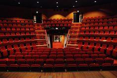 Theaterzaal met rode stoelen waar je ook van boven kan binnen komen met een lijst theater