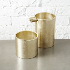 Shop seville gold cream and sugar set.   Modern cylindrical vessels serve up a unique twist on coffee/tea.  Casted from aluminum for a unique textured finish, set is finished in warm champagne gold.