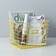 Crafted of sturdy steel wire with a durable yellow powdercoat finish, this tapered open storage bin holds and organizes household items with convenient carrying handles and ID label holder.