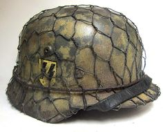 Reproduction Waffen-SS M35 Helmet in Normandy 1944 colours.   This is a double decal M1935 Helmet painted in RAL7009 with Swastica and SS Runes. It has be repainted in typical Normandy colour scheme. The M35 liner is early war aluminium and the worlds best copy. The chinstrap is aluminium buckled and early war version, it has a suitable repair with wire and has several deep age cracks.    http://www.warhats.com/store/p444/M35_Helmet_-_Waffen_SS_Normandy_with_Chicken_Wire.html…