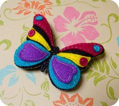 butterfly-think clay-use cookie cutter for base and then smaller cutters for colored bits and layer together and bake.  would make a nice pin: