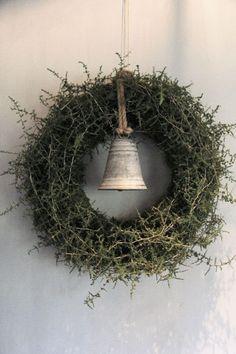 Krans van wilde asparagus met een zinken kerstklok als decoratie. Doorsnede van deze kerstkrans is 57 cm. In overleg zijn andere formaten mogelijk.