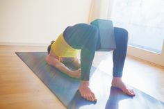 Yoga block with bridge pose. Using a block with bridge pose will encourage the inner thighs to draw toward one another