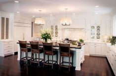 : Neat White Kitchen Set In Large U Shaped Layout With Dark Wooden Floor And Large Pendant Lighting Above Island