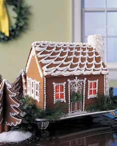 Snow-Swept Gingerbread Cottage    The caramelized-syrup windows of this colonial house are lit from within by a string of holiday bulbs, which flicker and glow like firelight.