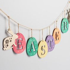 String up Easter cheer with our bright garland, crafted of laser-cut wood and hung from a jute cord. Its six lettered eggs are hand stained in vibrant colors, sprinkled with white polka dots and bookended by natural wood bunnies.