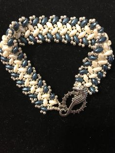 Hand beaded bracelet with ivory and blue super duo beads and silver seed beads with a antique silver seahorse clasp fits sizes 6 1/2-7 1/2