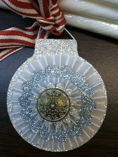 handmade paper ornament from All That Scrap ... tag that can hang on the tree ... silver glitter paper die cut to ornament shape ... vellum rosette ...  more glitter paper and an antique brad ... luv the sparkly icy look ... Stampin' Up!