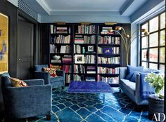 In the library of accessories designer Fiona Kotur's Hong Kong home, the pair of Christian Liaigre armchairs and the custom-made sofa and its pillows are all covered in Manuel Canovas fabrics | archdigest.com