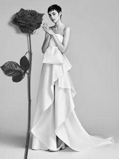 在上個月底推出的 2018 年春夏婚紗系列當中,Victor & Rolf 將一場婚禮當中更浪漫的符號都在婚紗上方美麗堆疊:銀河一般鋪排橫亙的細碎珠飾、垂瀑般向下傾瀉的貼花、以及擁有俐落邊緣的蝴蝶結及荷葉邊,全將人們對婚紗的極致想像以游刃有餘的藝術家工筆細膩刻畫。