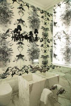 Tropicalismo no lavabo - o cômodo de mármore calacata gold recebeu, nas paredes, Toile de Jouy tropical em preto e branco, da Hermès