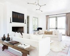 Coastal living room brings in the breeze with smaller coastal accents such as the white driftwood coffee table and glass jars (window sill) without overdoing it.