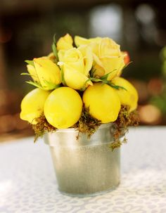 Bright yellow roses and lemons in a galvanized-tin pail.
