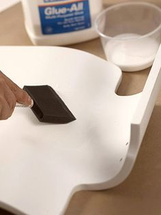 Step 3  Paint household glue (such as Elmer's) over the entire surface of the item using a foam brush. The glue should still be wet when the paper is positioned on the surface.  Tip: For a clean edge, trim any overlaps with a very sharp knife when the paper is dry and stiff with glue.