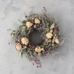 Dotted with lush, dried peony blossoms, this wreath brings home a meadow of artemisia, echinops, oregano, Spanish moss, eucalyptus, and nigella pods.