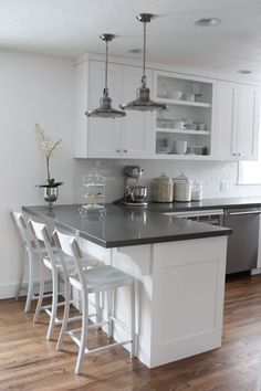 White cabinets, gray counters, wood floors, but I would add a color on the wall and a back-splash with a little color too.