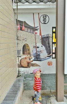 A boy in front of a piece of graffiti featuring the rat from the Chinese zodiac in a community park. Chinese Zodiac, Shenzhen, Rat, Graffiti, Tourism, Community, Entertaining, Vacation, Travel