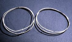 A pair of bangles: now oval in shape, each made of two tubular silver wires joined together on one side of the bangle for a distance of 2.5 cm. At the opposite side are two knobs which are part of the clasp; the bracelet was closed by pushing one end of a tube over the part of the tube which projected from the knob opposite. On one of the tubes there are two knobs; the other tube has one knob. The more mis-shapen bangle has traces of two seams running erratically along opposite sides of one…