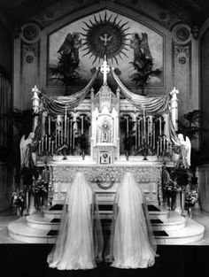 Two nuns in chapel veils praying before the Blessed Sacrament exposed in a   Monstrance