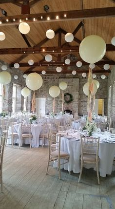 Giant balloons made the perfect centerpieces in this room, with white washed floors, exposed brickwork and high beamed ceilings. #rustic #wedding