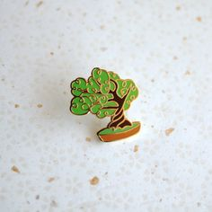 This little bonsai tree doesnt need any water or sunlight, but would love to adorn your lapel. A miniature of a miniature!  Finished in gold metal, the pin is 1 high and comes with a rubber clutch.