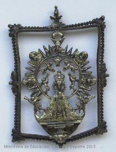 Medalla en plata con la figura de una Virgen rodeada por ángeles, dos de ellos trompeteros a los pies. CE02076