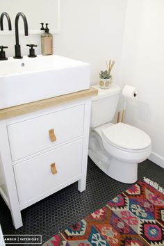Ikea sink cabinet and small black hex tile in a powder room