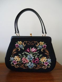 This black needlepoint purse is beautiful! It has a gold tone top clasp and two handles. The needlepoint is in great condition and is on the
