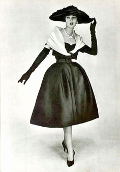 The model is showing Dior's black silk faille cocktail dress with a white organdy
