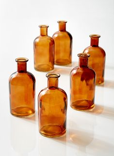 These amber glass medicine bottle bud vases make a nice accent for a table. Add different flowers to each, to create a unique grouping for a table centerpiece. Antique Glass Bottles, Glass Bottles With Corks, Brown Bottles, Amber Bottles, Amber Glass, Honey Bottles, Decorative Bottles, Colored Glass Vases, Colored Mason Jars