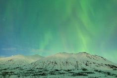 Display of Northern Lights (Aurora Borealis) over the Talkeetna Mountains at Hatcher Pass in Southcentral Alaska. Evening. Winter.