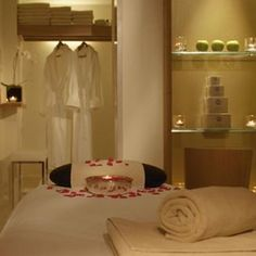 Massage Room...love the touch of flower petals and a candle on the bed!