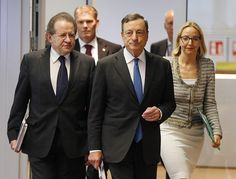 President of European Central Bank, ECB, Mario Draghi, center, is on his way to a news conference following the meeting of the Governing Council of the ECB in Frankfurt, Germany, Thursday, July 16, 2015. (AP Photo/Michael Probst)