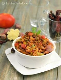 An very unique preparation of Mixed Pulses with Vegetables, this recipe combines moong, masoor and kala chana, with a radically different choice of vegetables, namely cauliflower, baby onions and tomatoes. A pungent masala paste imparts a lingering flavour to this subzi, while a simple garnish of coriander gives it a perky touch. Serve piping hot with rice or any Indian bread.