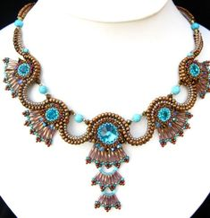 This necklace comprises waves of ash gold and bronze seed beads, embellished with waves of golden bronze bugle beads Turquoise gem beads and gold, blue and green Swarovski crystals and of course light blue Swarovski chatons and a center Turqoiuse Swarovski rivoli.