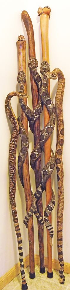 Rattlesnake walking sticks. Each walking stick is hand-carved from a single piece of wood, stained and painted.