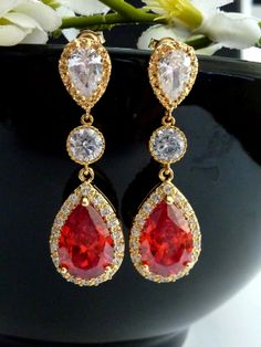 This classy earring features a LARGE red (with a touch of orange) peardrop cubic zirconia (20 X 15 mm clear back) with multi small zirconias around it, dangle from a round cubic zirconia connector, with a yellow gold plated peardrop cubic zirconia post earring..  Size: 4.5 x 1.5 cm or about 1.8 inches long.