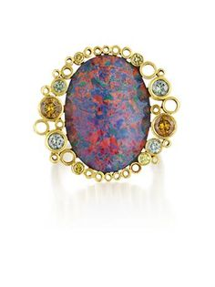 Smashing Opal, Diamond and Gold Ring from Cartier. Set with an oval cut black opal, within a polished gold tubular swirled surround, accented by circular-cut yellow/gold & blue colored diamonds, to the polished gold flat band, mounted in 18K yellow gold. Signed 'Cartier', with original box.