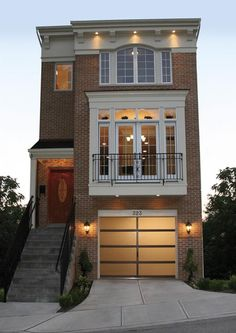 Clopay Avante Collection glass garage door. You may be pleasantly surprised to find this modern look isn't exclusive to modern digs. It can be a unique focal point on a traditional home as seen on this three story row house. www.clopaydoor.com