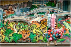©Lawrence Ho/The Los Angeles Times  East Los Angeles Downpour A man with an umbrella passes a colorful mural on the wall of an East Los Angeles are neighborhood during a rainstorm. The moment resembles a Cezanne Painting when viewed through the waterlogged car windshield. Rain is always a news event in Los Angeles.