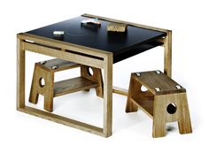 FRAME table natural oiled oak with black Fundermax topplate used as kids table sitting on STOOL. Notice that the tabetop can be used as a chalkboard to draw directly upon.