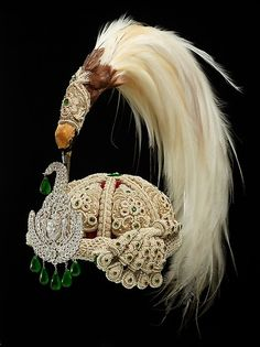 Jeweled Crown, 1900, Nepal.  Pearls, colored glass, diamonds, emeralds, and rubies, with gold brocade ribs and bird of paradise plumes; interior lined with red cloth Overall: H. (with plume) 16 1/8 in.; cap: H. 6 1/4 in., Diam. 9 1/2 in.; plaque: H. 7 1/8 in., W. 4 1/8 in. Via The Al-Thani Collection.