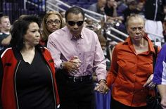 """Muhammad Ali, center, is escorted into the US Airways Center by his family, including his wife Lonnie, right, just before U of L's NCAA tournament game against Michigan State in Phoenix, Az. Mar. 22, 2012. """"The Greatest"""" was there for the game."""