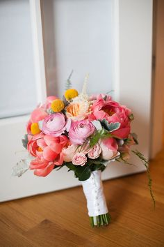 A bright bouquet of peonies, ranunculi, and billy buttons | Photo by Artistrie Co.
