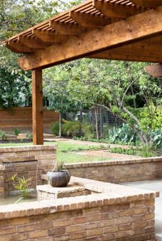 Wood Pergola Covering a Salt Finished Concrete with Brick Seat Wall. I like that idea of salt finished perhaps it would keep weeds from popping up.